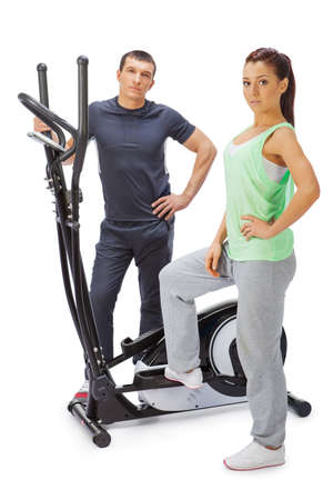 Young man and woman with elliptical cross trainer. photo