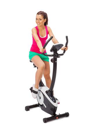 La mujer joven utiliza entrenador bicicleta estacionaria.