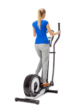 cut outs: Young woman uses elliptical cross trainer. Stock Photo