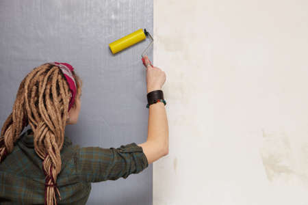 Young woman primed the wall. photo