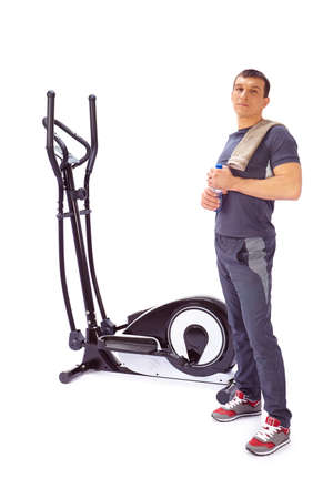 tracksuit: Young man uses elliptical cross trainer.