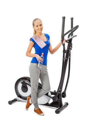 elliptical: Young woman uses elliptical cross trainer. Stock Photo