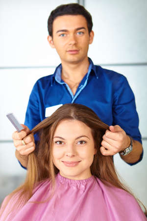 Hair salon. Woman haircut. Combing. photo