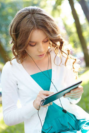 palmtop: Young woman listens music using tablet pc.