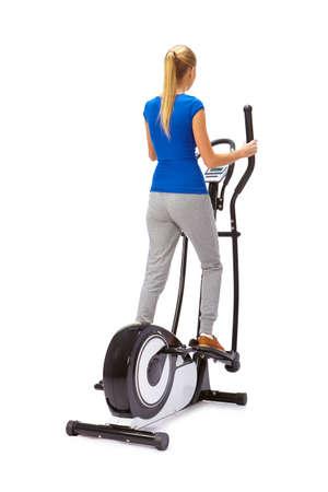 eliptica: La mujer joven utiliza la máquina elíptica. Foto de archivo
