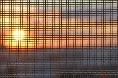 Puesta de sol a través de la mosquitera Foto de archivo