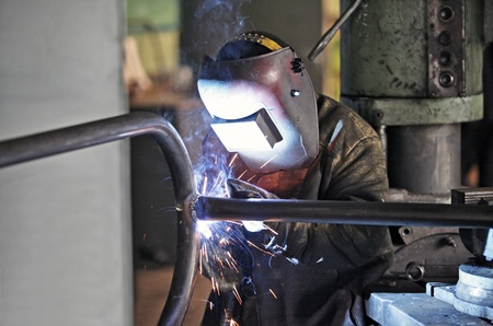 skilled labour: Welder welding pipes Stock Photo