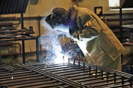welding metal: Welder welding pipe grid