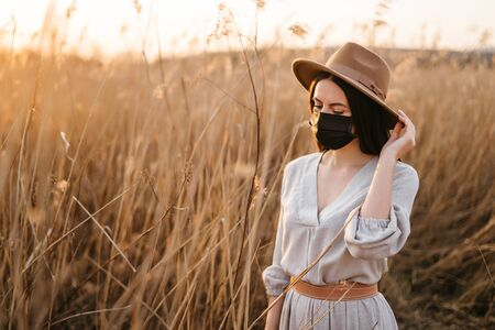 Portrait of a young woman in a beige hat and a protective mask on a walk alone