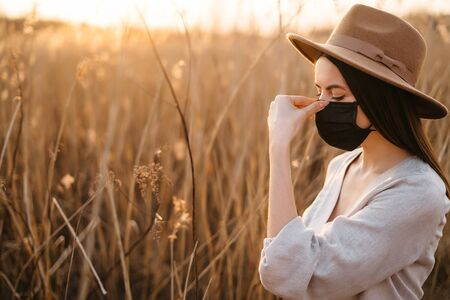 Portrait of a young woman in a beige hat and adjusts her face shield while walking alone Stockfoto