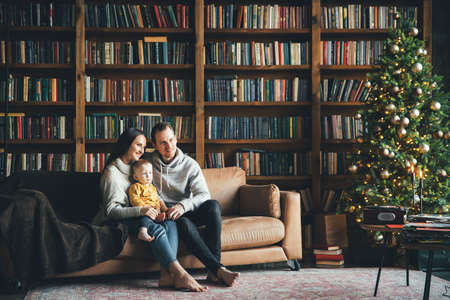 Happy family at home in cozy living room with a decorated festive Christmas tree 版權商用圖片