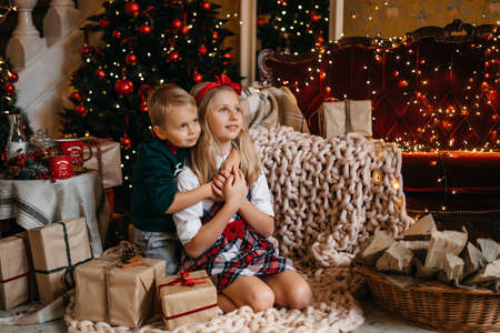 Little boy and girl are sitting near the Christmas tree and hugging. Happy brother and sister. High quality photo