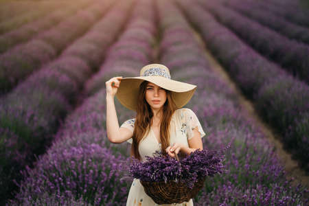 A young and happy blonde woman in a delicate dress and a straw hat is enjoying the spring in a lavender field at sunset, holding a basket full of flowers in her hands. High quality photo
