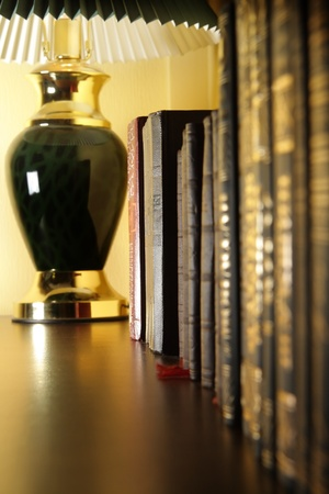 Old books in a row at the lamp photo