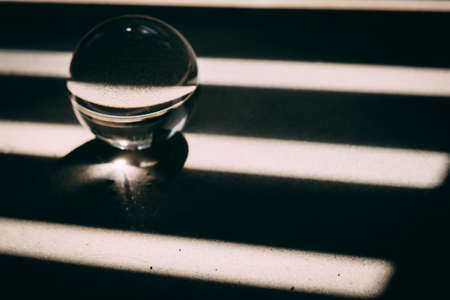 glass transparent ball rolls along dark and light lines, light and shadow. the concept of good luck and bad luck in life. 免版税图像
