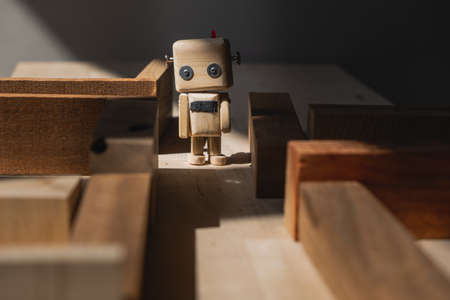 small wooden robot in a maze of wooden blocks. path selection concept