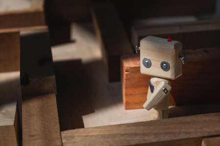 small wooden robot in a maze of wooden blocks. the concept of finding the right solution