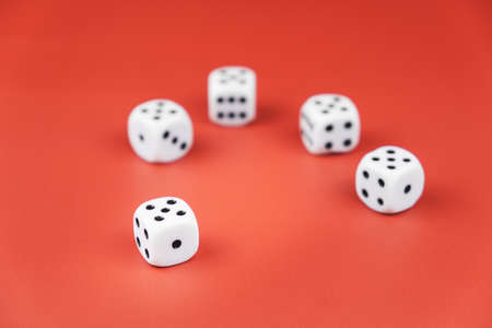 five dice lie on a red background. all the bones have fives. rare luck