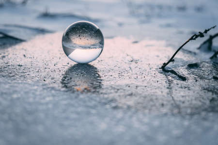 glass transparent ball on an ice crust in winter, reflected on ice. dawn