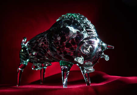 Illuminated glittering crystal glass bull on red velvet close up Stock Photo