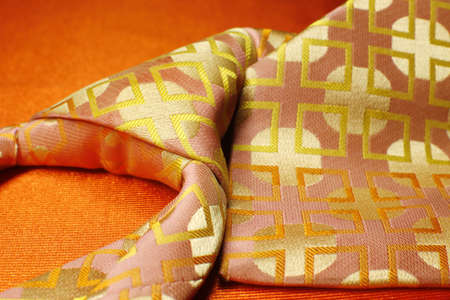 Bright pink with yellow necktie on orange background, fashion accessory close up Stock Photo