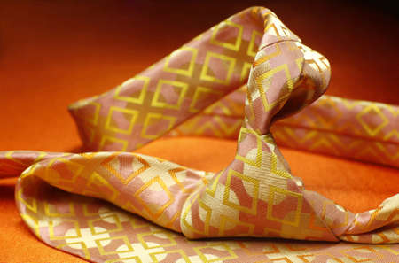 colourful tie: Bright pink with yellow necktie on orange background, fashion accessory close up Stock Photo