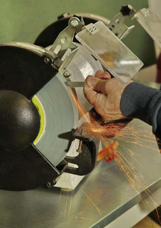 wheel spin: Manual sharpening of a tool on grinding machine with sparks close up Stock Photo