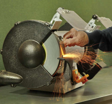 Manual sharpening of a tool on grinding machine with sparks close up Stock Photo