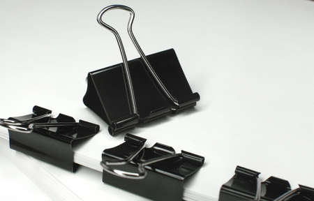 Black binder clips clamping the paper close up white background