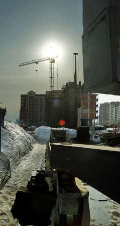 industrial district: Under construction high-rise building with yellow construction crane in the sunlight