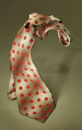 colourful tie: Brown with red spotted necktie on green fabric background, fashion accessory close up Stock Photo