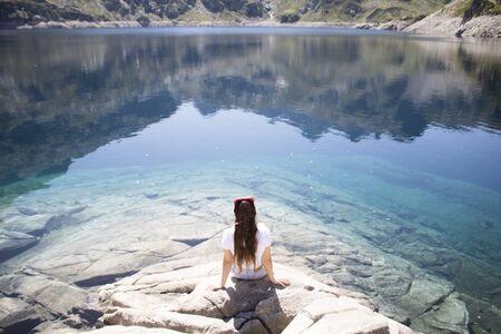 Girl sitting in front of a lake 版權商用圖片