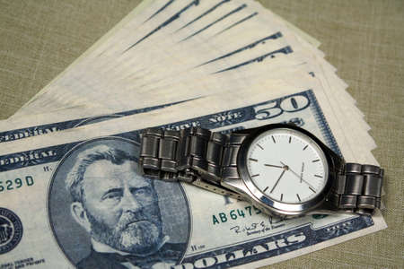 Some fifty dollars notes and watch with white clock face photo