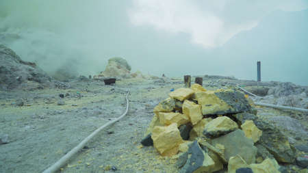 Extraction of sulfur in the crater of a volcano. Sulfur gas, smoke. Kawah Ijen, crater with acidic crater lake where sulfur is mined. Ijen volcano complex is a group of stratovolcanoes in the Banyuwangi Regency of East Java, Indonesia. Stock Photo