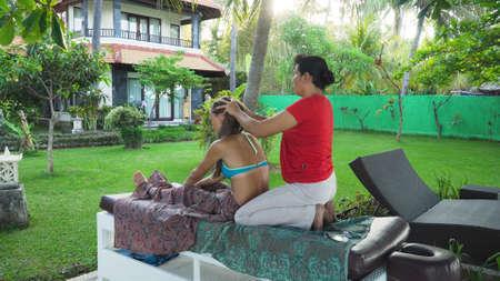 Asian woman massage therapist doing massage to girl. Summer vacation on luxury spa resort, massage procedure on the beach. Young woman enjoying a massage outside. Bali,Indonesia. Stock Photo