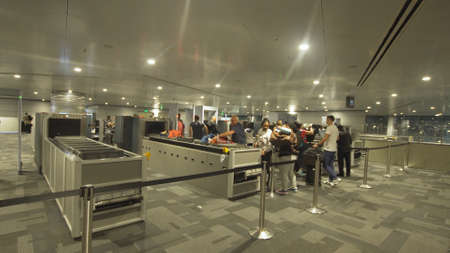 Bali, Indonesia - October 15, 2017: People wait in the security line at Hamad International Airport in Doha. Security and passport control, X-ray scanner and metal detector at security checkpoint in Airport .