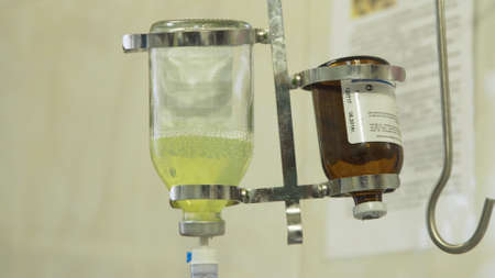 Dropper for intravenous injection. Apparatus and valve control for saline solution to patient. Infusion pump iv feeding.