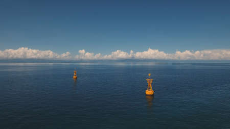 Orange buoy in the blue sea on a background of blue sky, clouds, island. Aerial view:navigational buoy in the ocean.Philippines, Cebu. Travel concept.