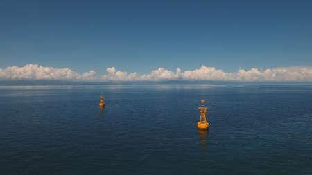 青い空、雲、島を背景に青い海のオレンジ色のブイ。航空写真:海のナビゲーションブイ。フィリピン、セブ。旅行のコンセプト。