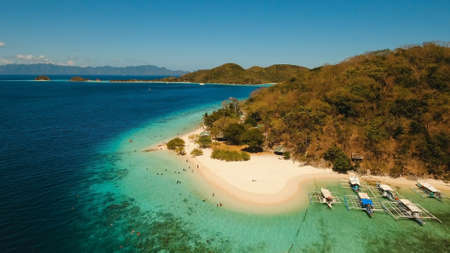 Aerial view of tropical beach on the island Banana, Philippines. Beautiful tropical island with sand beach, palm trees. Tropical landscape: beach with palm trees. Seascape: Ocean, sky, sea. Travel concept.