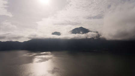 Mountains, volcanoes, crater lake Batur at sunrise, Bali, Indonesia. Mountain landscape with volcanoes, lake, sky and clouds. Travel concept