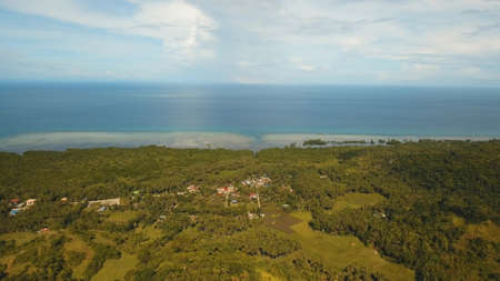 The town near the sea, houses, buildings, port. Aerial view coastal city nn the island of Bohol near the sea. Seascape with a town and the sea. Travel concept. Stock Photo