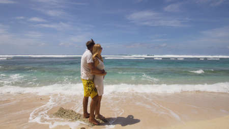 Beautiful couple embracing each other stands on the beach and looks at the sea.Relationships, Beach, couple on romantic travel honeymoon vacation summer holidays romance. Young happy lovers. Travel concept. Bali.