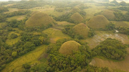 Amazingly shaped Chocolate hills on sunny day on Bohol island, Philippines. Aerial view Chocolate Hills in Bohol, Philippines are earth mounds scattered all over the town of Carmen. Travel concept. Stock Photo