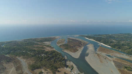 Aerial view of rver flowing into the sea in Philippines,Luzon. ropical landscape with sandy coast and river among farmer fields flowing into the blue ocean