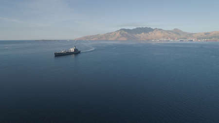 Aerial view: Cargo, Reefer ship in the sea bay. Subic Bay, Philippines, Luzon. Cargo ship in the harbor, against the backdrop of the mountains. Stock Photo