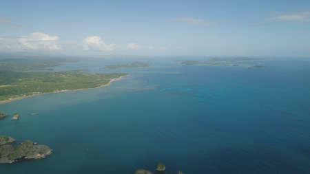 Aerial view of Groups islands with sand beach and turquoise water in lagoon among coral reefs, Caramoan Islands, Philippines. Mountains covered with tropical forest.