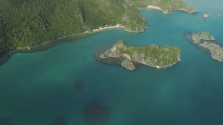 Aerial view island with sand beach and turquoise water in lagoon among coral reefs, Caramoan Islands, Philippines. Landscape with sea, tropical beach. Stock Photo