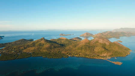 Aerial view: beach, tropical island, sea bay and lagoon, mountains with rainforest, Busuanga, Palawan. Seascape, tropical landscape. Azure water of lagoon Philippines