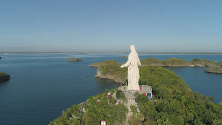 Statue of Jesus Christ on Pilgrimage island in Hundred Islands National Park, Pangasinan, Philippines. Aerial view of group of small islands with beaches and lagoons, famous tourist attraction, Alaminos.
